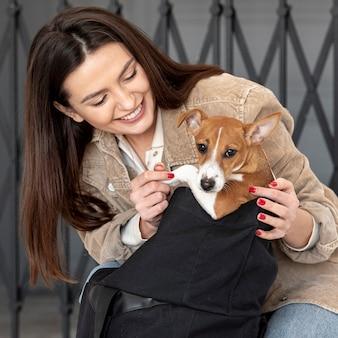 Frau, die mit ihrem hund aufwirft und lächelt