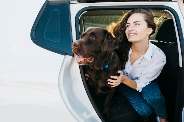 Frau, die mit ihrem hund im offenen stamm sitzt