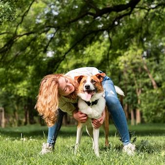 Frau, die mit ihrem hund im park spielt