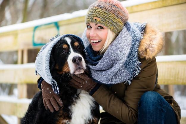 Frau, die mit ihrem hund im schnee spielt