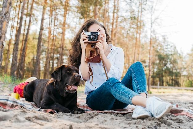 Frau, die mit ihrem hund in der natur sitzt