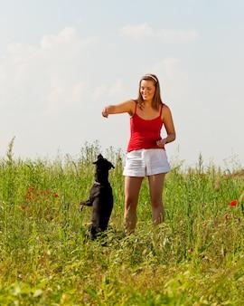 Frau, die mit ihrem hund in einer wiese spielt