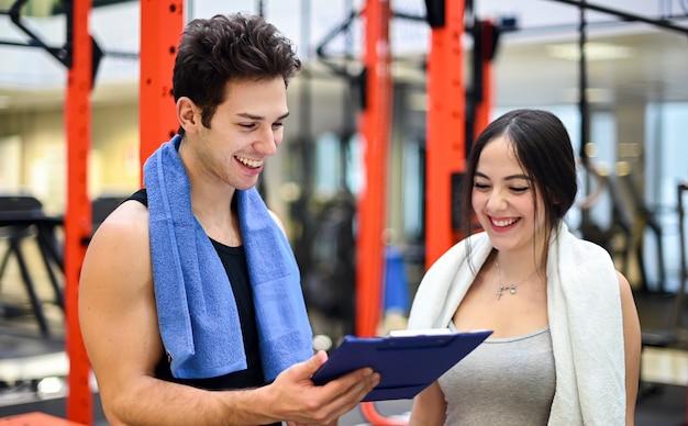 Frau, die mit ihrem persönlichen trainer in einem fitnessstudio spricht