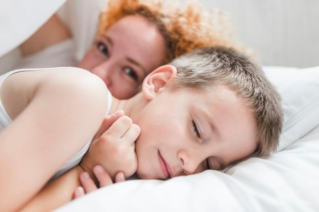 Frau, die mit ihrem schlafenden sohn auf bett liegt