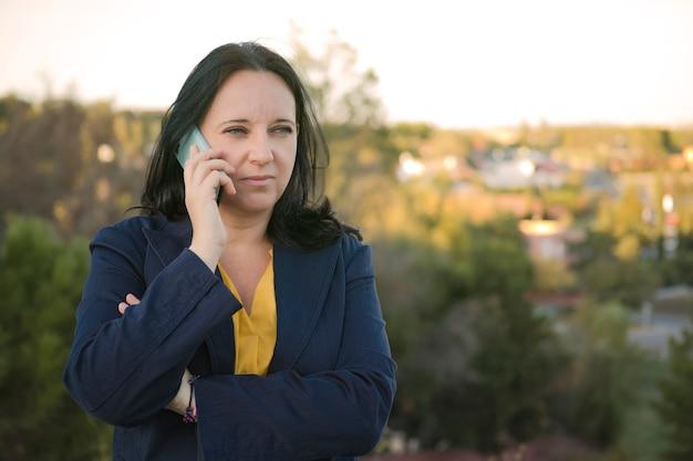 Frau, die mit ihrem smartphone auf der straße anruft.