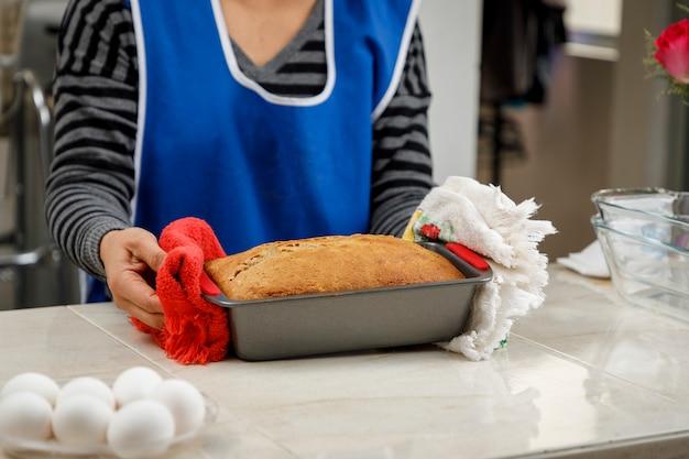 Frau, die mit ihren händen einen pfannkuchen aus dem ofen nimmt