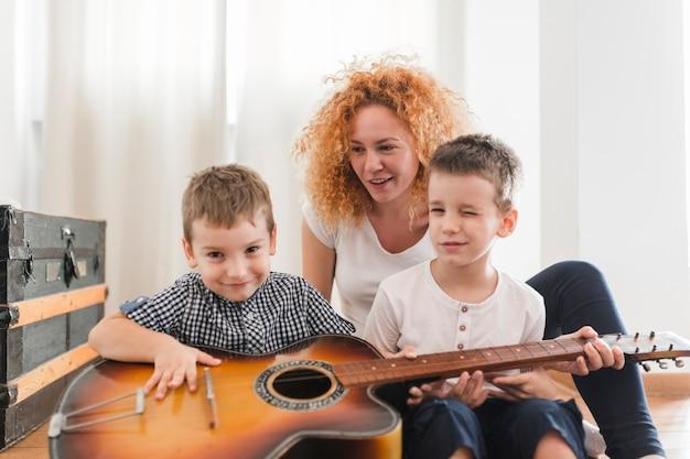 Frau, die mit ihren kindern spielen gitarre sitzt