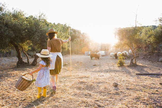 Frau, die mit ihren töchtern in herden leben auf dem gebiet geht