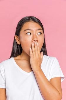 Frau, die mit ihrer hand auf ihrem mund überrascht schaut
