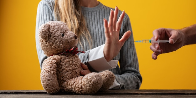 Frau, die mit ihrer hand eine stopp-geste in richtung eines impfstoffs macht, während sie ihren teddybären in einem konzeptionellen bild schützt.
