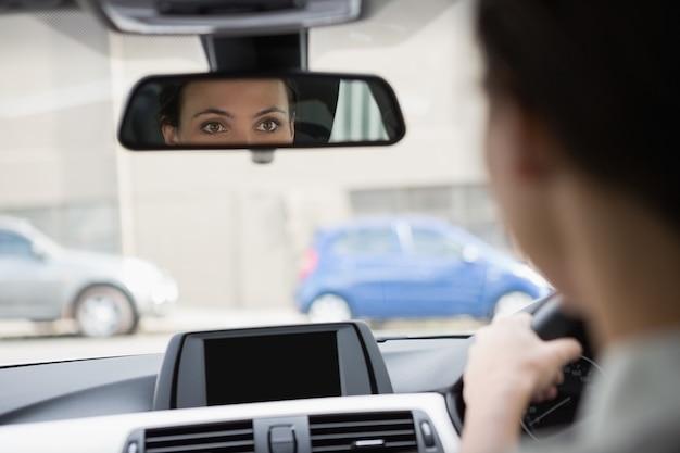 Frau, die mit ihrer reflexion im spiegel fährt