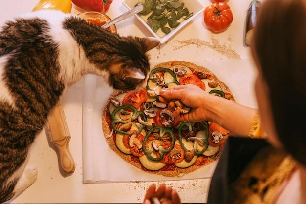 Frau, die mit ihrer süßen katze köstliche pizza zubereitet. hausgemachtes konzept.