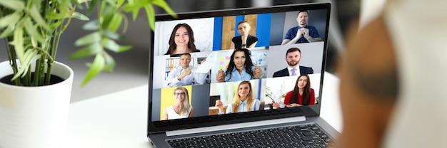 Frau, die mit internationalen kollegen spricht, die online-video-chat-dienst am arbeitsplatz verwenden