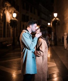 Frau, die mit jungem mann auf promenade am abend umfasst und küsst