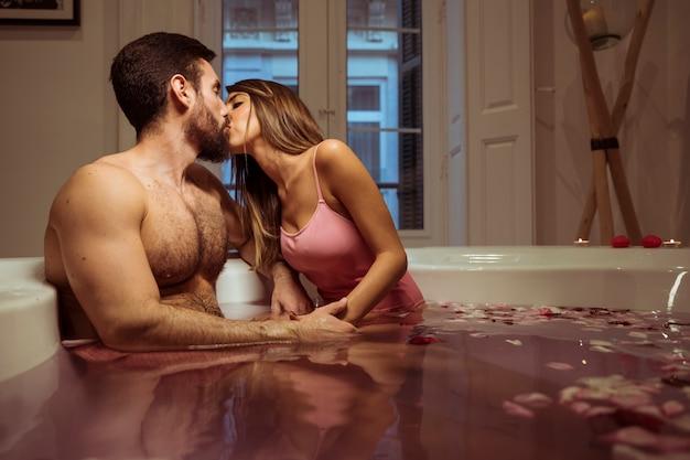 Frau, die mit jungem mann in der whirlpoolwanne mit wasser küsst