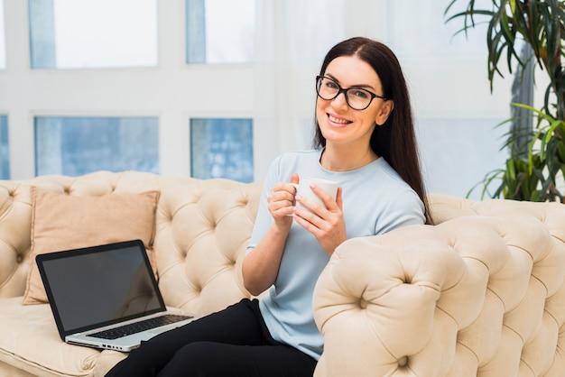 Frau, die mit kaffee und laptop auf couch sitzt