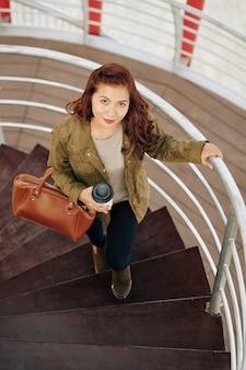 Frau, die mit kaffeetasse geht