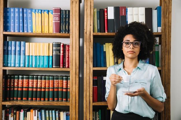 Frau, die mit kaffeetasse in der bibliothek steht