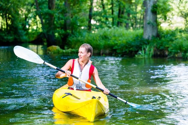 Frau, die mit kanu auf waldfluß schaufelt