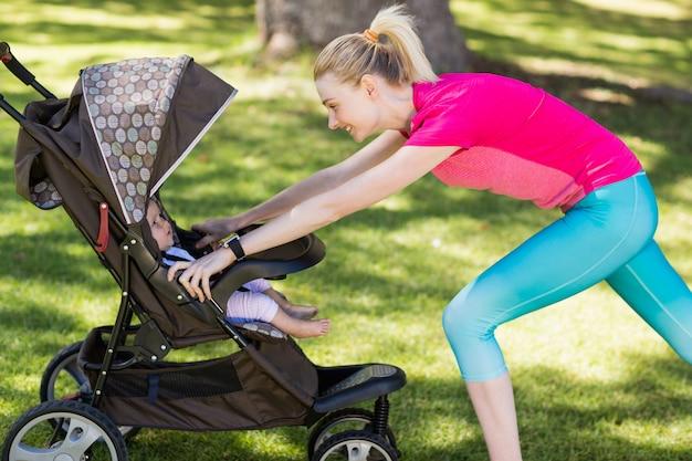 Frau, die mit kinderwagen trainiert