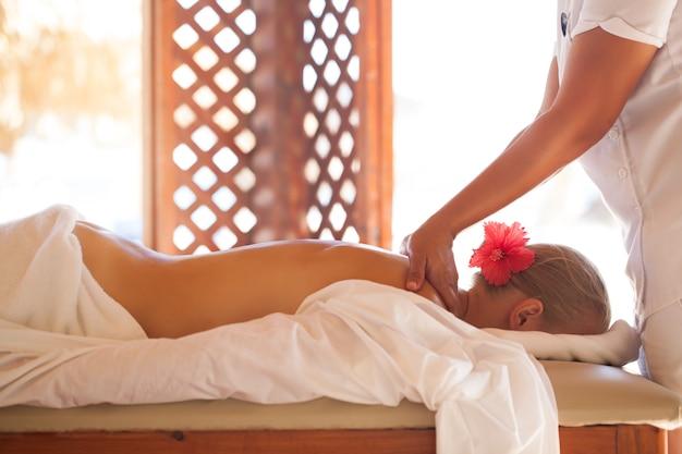 Frau, die mit körpermassage am schönheitsbadekurort sich entspannt