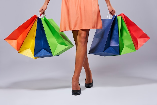 Frau, die mit koloful einkaufstaschen geht