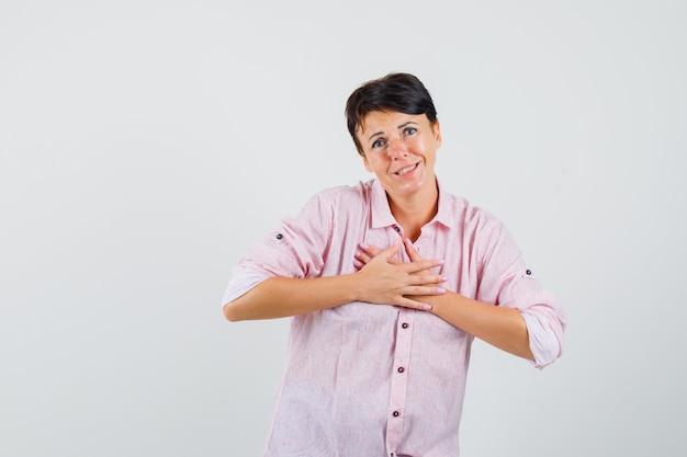 Frau, die mit kompliment oder geschenk im rosa hemd zufrieden ist und dankbar aussieht, vorderansicht.