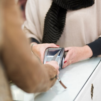 Frau, die mit kreditkarte durch anschluss zahlt