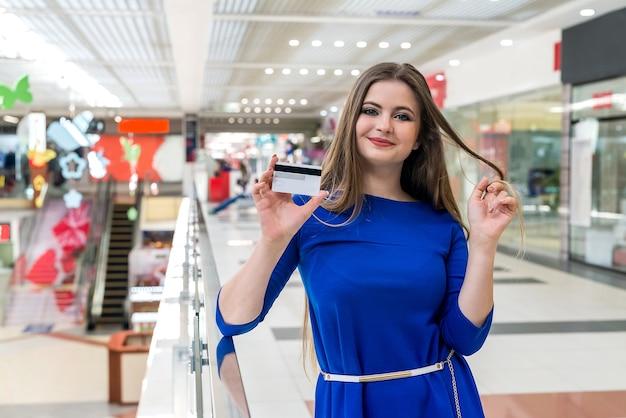 Frau, die mit kreditkarte im einkaufszentrum einkaufen geht