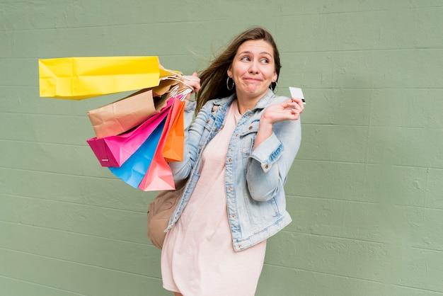 Frau, die mit kreditkarte und einkaufstaschen an der wand steht