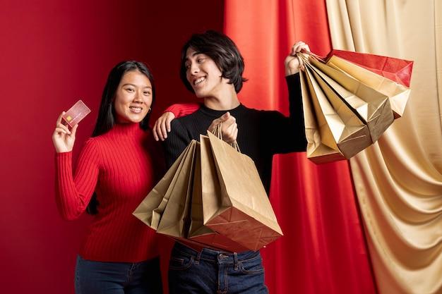 Frau, die mit kreditkarte und mann für chinesisches neues jahr aufwirft