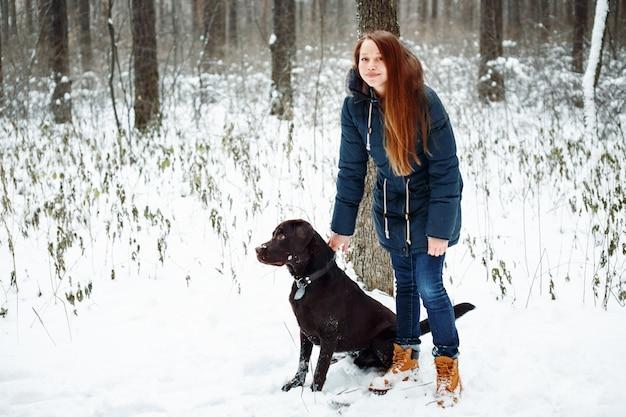 Frau, die mit labrador-hund im wald geht