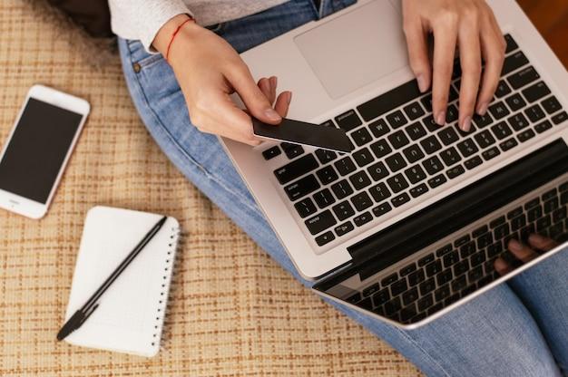 Frau, die mit laptop arbeitet und leere bankkarte hält