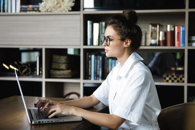 Frau, die mit laptop in ihrem büro arbeitet