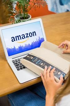 Frau, die mit laptop sitzt und lieferpaket öffnet