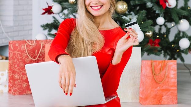 Frau, die mit laptop und karte nahe weihnachtsbaum sitzt