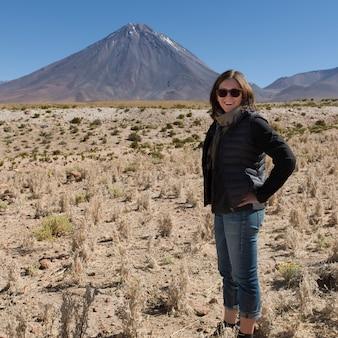 Frau, die mit licancabur-vulkan im hintergrund, salar de atacama, san pedro de atacama, el loa steht