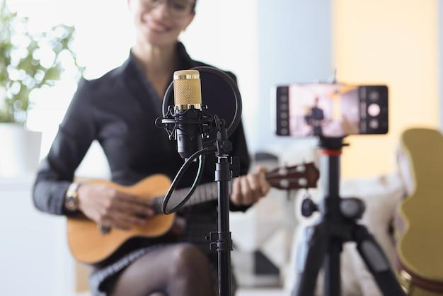 Frau, die mit mikrofon sitzt und ukulele vor kamera nahaufnahme hält. freiberufliches blogging-konzept