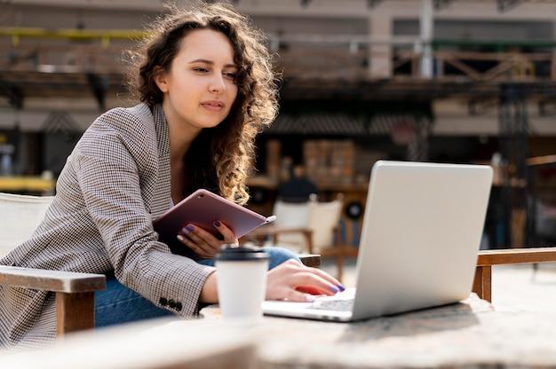 Frau, die mit mittlerem schuss des laptops arbeitet