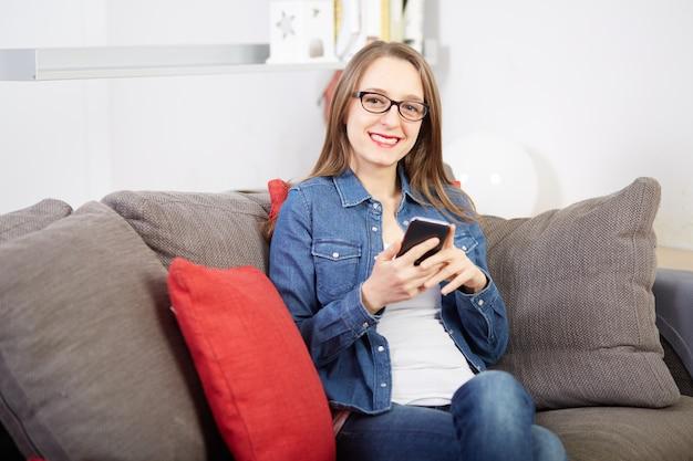 Frau, die mit mobile auf sofa spricht