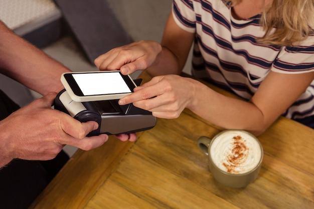 Frau, die mit mobiler zahlung zahlt