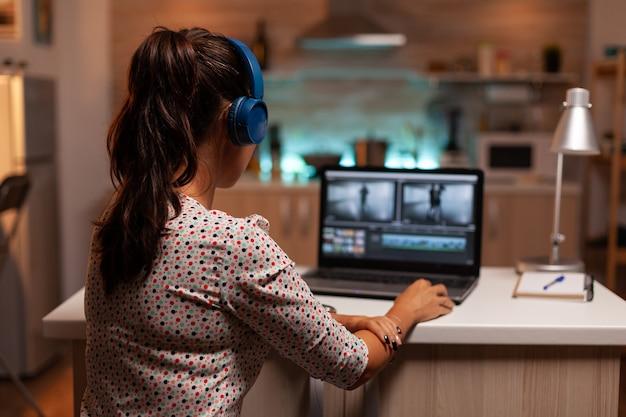 Frau, die mit moderner software mit videomaterial auf laptop arbeitet. inhaltsersteller zu hause, der an der montage von filmen mit moderner software für die späte nachtbearbeitung arbeitet.