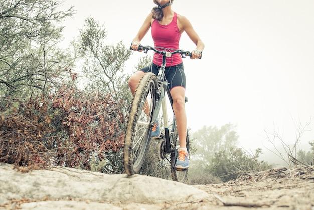 Frau, die mit mountainbike bergab macht. konzept über menschen und sport