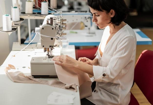 Frau, die mit nähmaschine arbeitet