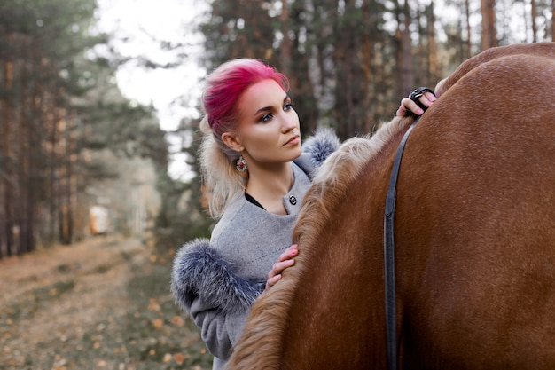 Frau, die mit pferdeherbst auf natur geht. kreatives make-upmädchengesicht des heißen rosas, haarfarbton. portrait eines mädchens mit einem pferd. reiten im herbstlichen wald. herbstkleidung und helles rotes make-up