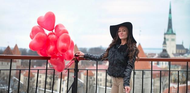 Frau, die mit roten herzballons geht. altstadt von tallinn. valentinstag-konzept. panoramablick