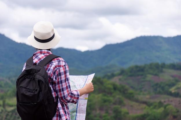 Frau, die mit rucksacktourist hält, der karte betrachtet berg in der regenzeit hält