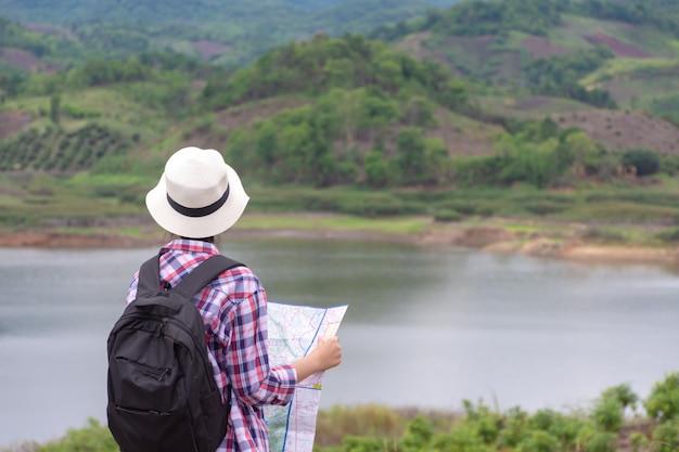 Frau, die mit rucksacktourist hält, der karte betrachtet, die berg und see betrachtet