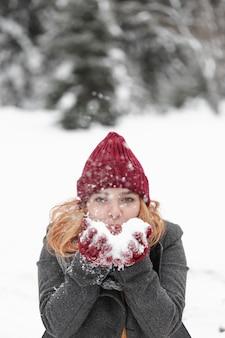 Frau, die mit schnee draußen spielt