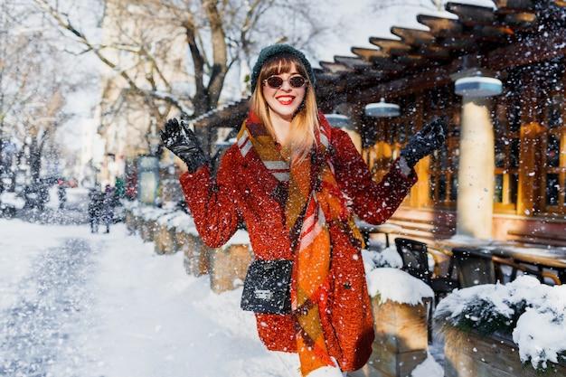 Frau, die mit schnee spielt, spaß hat und feiertage genießt